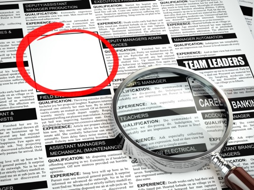 Job search concept. Loupe, newspaper with employment advertisements.